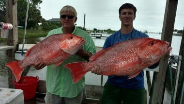 Father and son holding red snappers